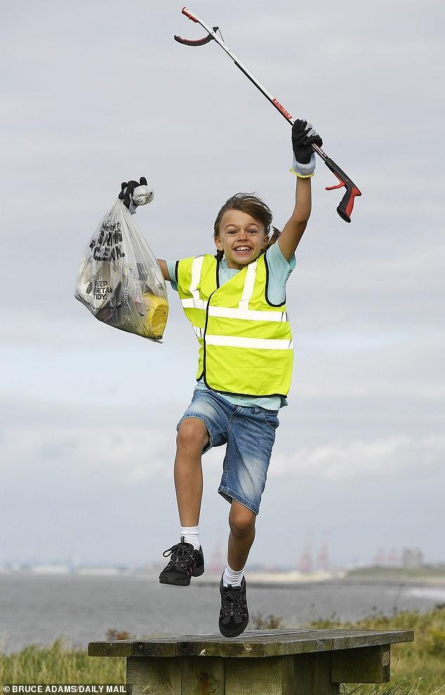 Elizabeth Gadsdon, nine, picks litter on the coast at Leasowe lighthouse, Wirral, Merseyside