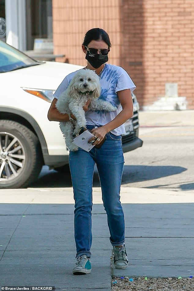 Casual: The actress looked on trend in a tie dye t-shirt that she wore tucked into the top of blue jeans. She wore her hair tied back from her face and donned sunglasses and a black face mask