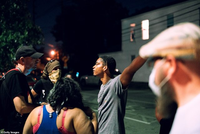 Protesters gather outside a local bar in defiance of a city-wide curfew on Sunday in Louisville, Kentucky. The mandatory 9:00pm to 6:30am curfew followed Kentucky Attorney General Daniel Cameron's announcement of charges against an officer involved in the death of Breonna Taylor