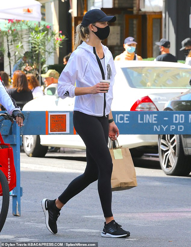 Outfit: The model donned a white jacket and a matching vest for the outing along with a pair of black leggings