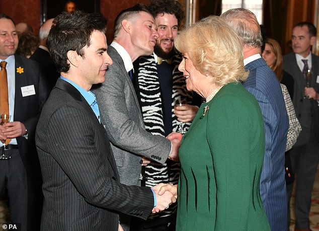 The Duchess of Cornwall speaks with Kelly Jones, lead singer of the Stereophonics, at a reception at Buckingham Palace in London to mark the fiftieth anniversary of the investiture of the Prince of Wales in 2019