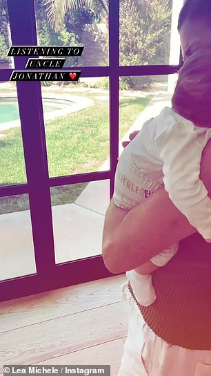 'Listening to Uncle Jonathan!' Lea's six-week-old son was being rocked seemingly by her husband Zandy Reich, Ever's father