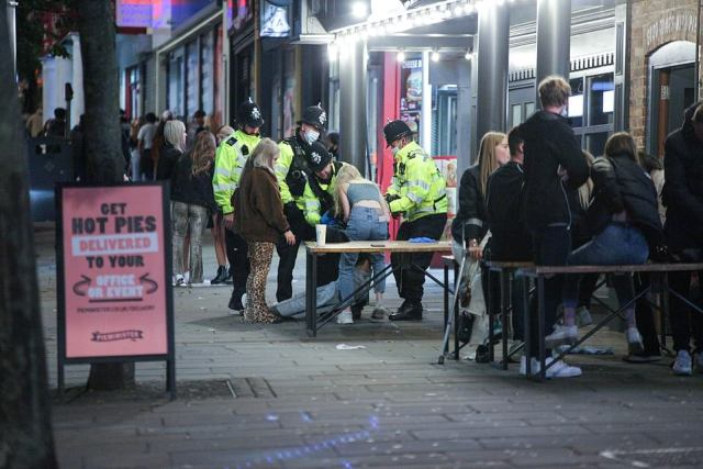 Drinkers pictured on the street in London after they were kicked out of pubs due to curfew