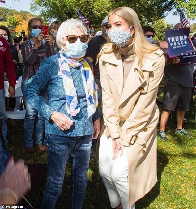 Smiling behind the mask: Ivanka squatted down to pose with one woman during the visit