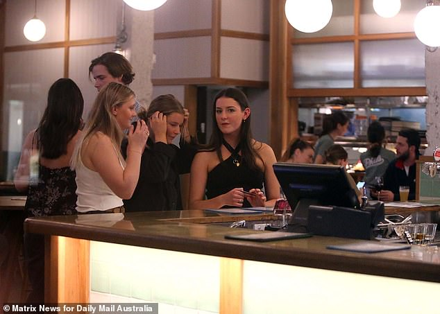 Food and beverage sales have been down 60 per cent as a result of having just one patron per four square metres (pictured friends visit a bar in Sydney)