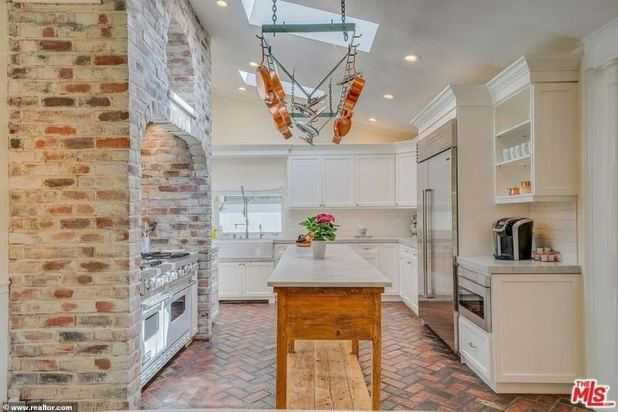 What's cooking?  Kitchen is also easy on the eyes with white cabinets and gray counters with washed brick cover for double shelves