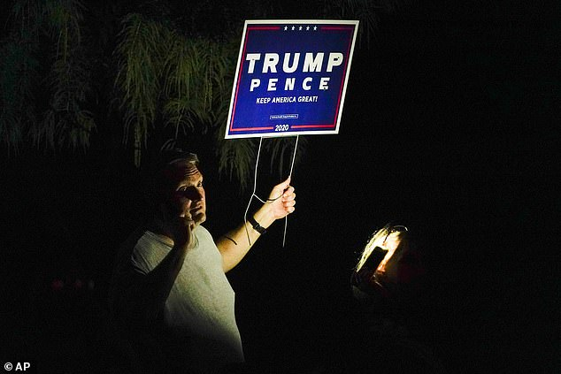 A supporter of President Donald Trump stands outside the private residence where Democratic presidential candidate former Vice President Joe Biden is staying for a short time in Cleveland