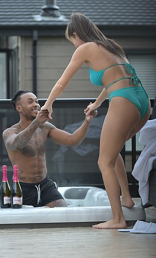 Easy does it! Biggs was seen helping his girlfriend into the hot tub
