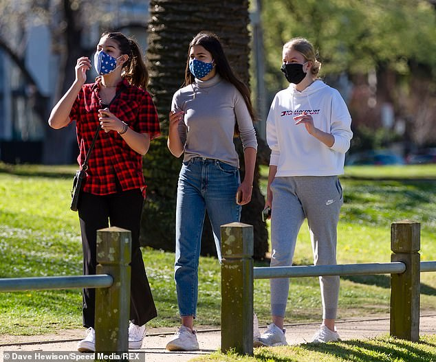 Young women are seen walking together along a track by Princes Park in Melbourne on Monday. An inquiry into Victoria's hotel quarantine program has heard 768 people have lost their lives in the state to COVID-19 because of the botched regime