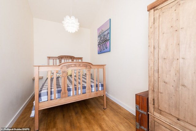 The light and airy double bedroom has a raised ceiling, wooden floors and just enough space for a double bed and a wardrobe for beachwear clothes