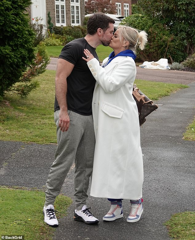 Smooch:The TV personality enjoyed a leisurely walk with her beau on Wednesday and they shared a passionate kiss as they continue to celebrate their recent engagement