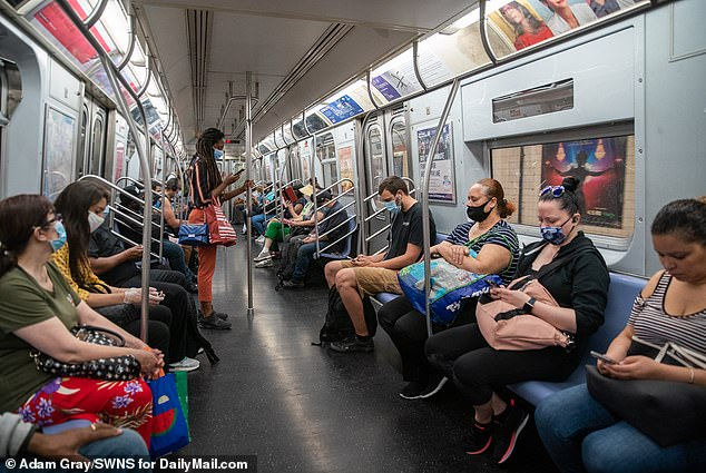 Academics argue such cleaning measures were not in place during the early days of the pandemic, which is what helped spread the virus. Pictured: People ride the L train subway during rush hour in New York City, June 8
