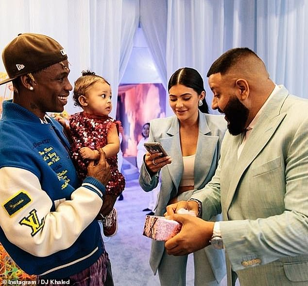 Blessed: Rapper DJ Khaled also surprised Stormi with her first Chanel accessory at her first birthday party last year (pictured with the little girl's father, Travis Scott)