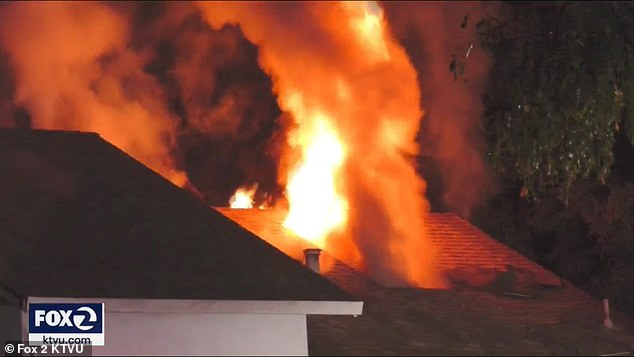 Flame are seen pouring out the top of the Fremont home on Tuesday morning