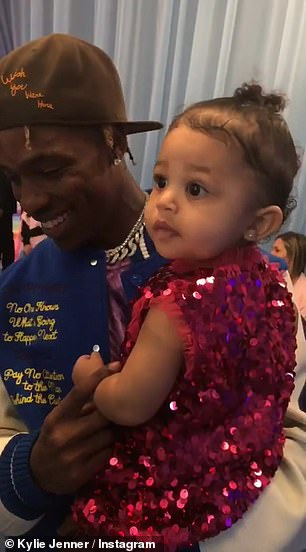 Stormi watched with her father Travis as Khaled unwrapped the glittery pink paper, revealing the pint-sized red velvet purse