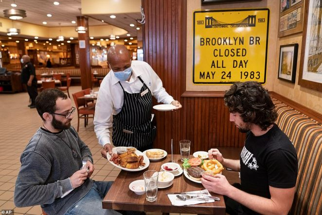 Waiter Lenworth Thompson serves lunch to David Zennario, left, and Alex Ecklin at Junior's, a chain restaurant, on Wednesday