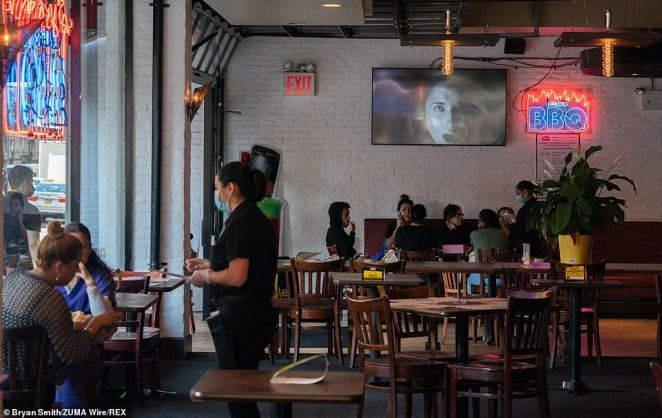 A waitress tends to a table at Dallas BBQ in Chelsea as New York City restaurants reopen for dining limited to 25 percent seating capacity