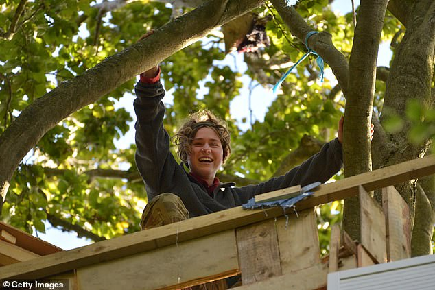 A HS2 protester looks from her treehouse as the tree protection camp faces eviction by the NET