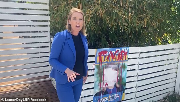 LNP candidate Lauren Day (pictured), 38, standing next to a campaign sign that has been graffitied with the word 'racist' in the Brisbane state electorate of Maiwar on Friday