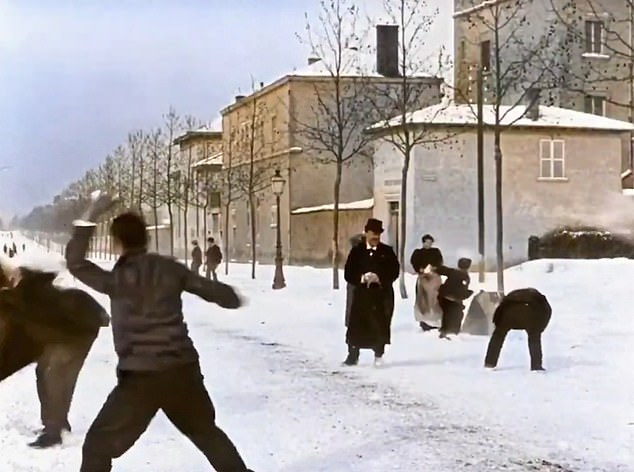 A man makes a ball with the snow he has just picked up as another person prepares to shoot his snowball