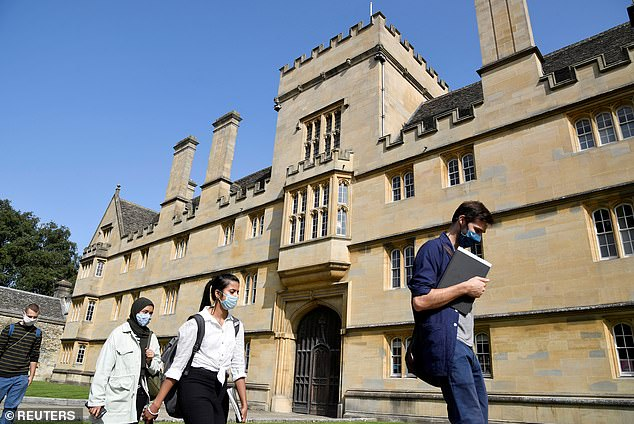 New normal: Students wear face masks outside Oxford University's Wadham College last month