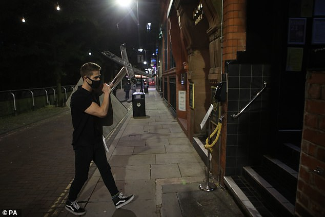 A staff member wearing a protective face covering clears away a table for the evening in Manchester