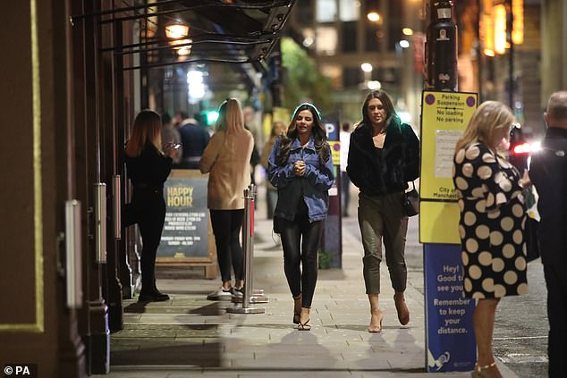The Prime Minister is expected to address Parliament tomorrow to reveal the new nationwide three-tier system of restrictions as cases continue to rise. Pictured:Revellers in Manchester tonight