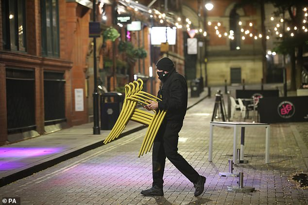 Chairs are stacked and moved away by a worker ahead of a potential lockdown in Manchester