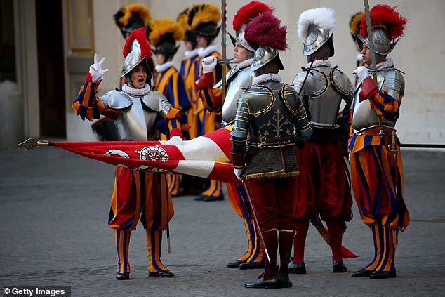 An elite recruit of the Vatican Swiss Guard raises three fingers, a sign of the Holy Trinity, during the swearing-in ceremony for new members at the Cortile di San Damaso on October 4