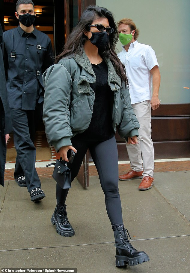 New Look: Later they were seen coming out of another building. Kourtney wore shiny black leggings with a black top with an army green bomber jacket and the same chunky military boots