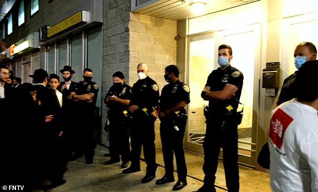 Masked police officers at the scene where hundreds of Hasidic men gathered on Sunday night