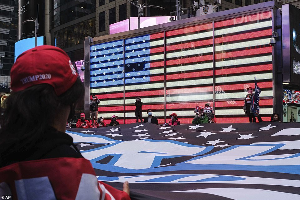 Supporters of President Donald Trump pause at Times Square Tuesday with a 75ft by 50ft flag