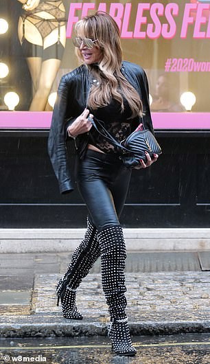 Dressed to impress: She finished her look withthigh-high suede boots covered with silver studs