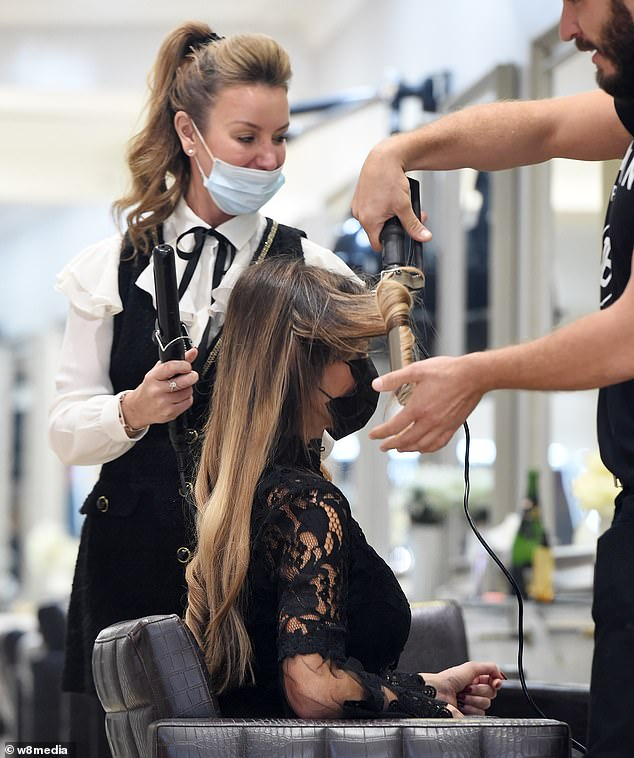 Time for a change? Lizzie donned a black face mask as two hairdressers styled her long hair into bouncy waves