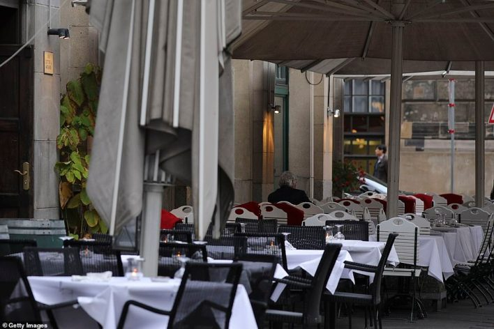 GERMANY: Empty tables outside a restaurant in Berlin, one of the cities which last week agreed new restrictions with Angela Merkel