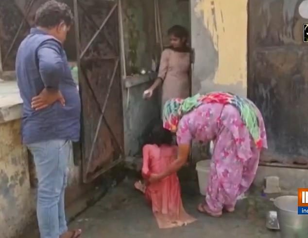Pictured: The 35-year-old woman being rescued from the 3ft by 3ft toilet on Tuesday in Panipat, India