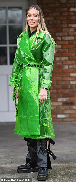 Bright:Demi wore a bright green trench coat with belted black flared trousers