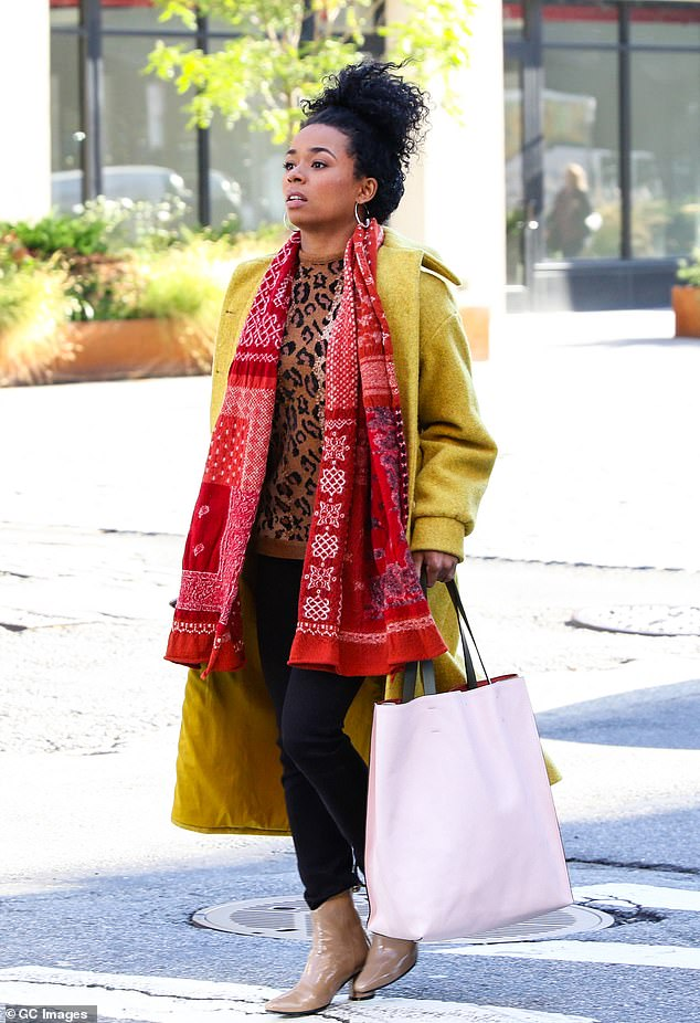 Staying warm: Alexis, who plays an aspiring filmmaker and concierge in the series, was seen on set in a brown leopard print sweater with a long red scarf, a yellow overcoat, dark jeans and beige boots