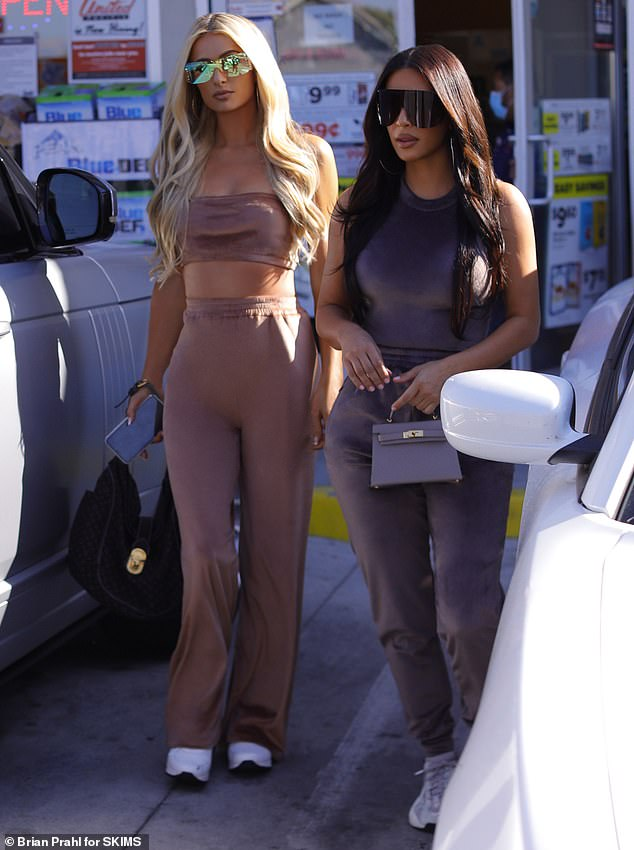 Double trouble: Kim looked chic in a soft purple velour tank top and matching sweatpants as she held a mini purse by Hermes. Paris opted for the dusty pink crop top and sweatpants while she carried a black bag and had on sneakers with mirrored sunglasses