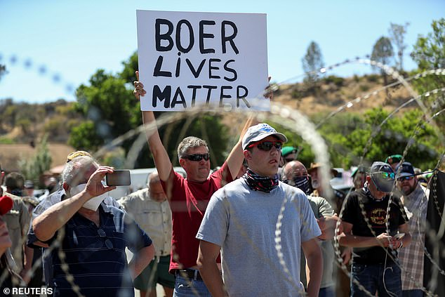 White protesters stand near barbed wire with a man holding a 'Boer Lives Matter' sign, a reference to the white population who own most of South Africa's farmland