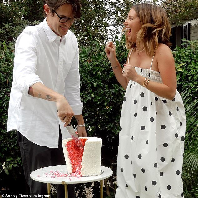 Big news: She and her husband Christopher French, 38, cut in to reveal a reddish-pink cake. The photos were at least two weeks old, as she tease them early in the month