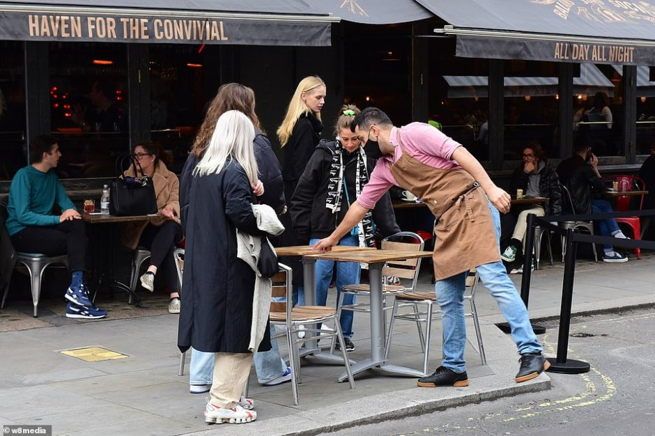 Revelers are brought to an outside table as a waiter asked them to give their details for Track and Trace.The decision to place London into a Tier Two lockdown today sparked fears around 200,000 people in the city's centre could lose their jobs in hospitality this weekend