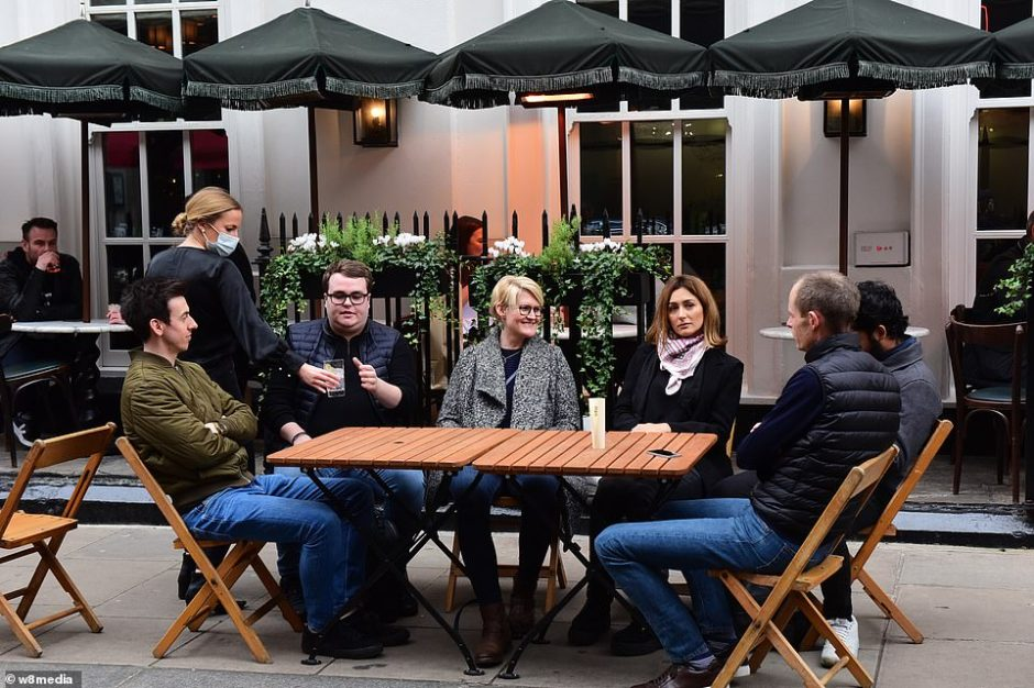 A group of six are served their drinks as they sit outside a bar in Soho, London, on the final night before restrictions are ramped up in the capital