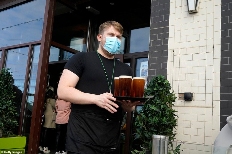 Lancashire joins Liverpool as the only areas in the top bracket, which means a ban on household mixing indoors and in gardens. Pictured, a barman serves drinks at a weatherspoons pub on the Blackpool promenade