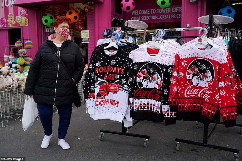A woman wears a face mask as she walks past a display rack featuring Christmas jumpers in Blackpool ahead of its move to Tier 3 restrictions