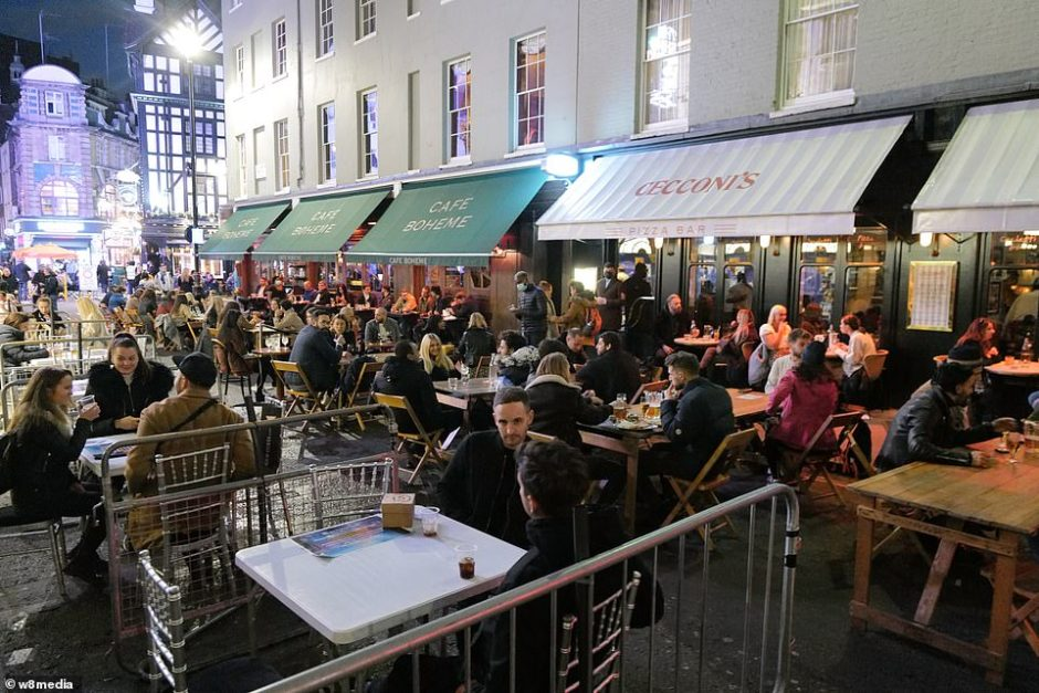 The tough social distancing rule mirrors what is in place in Covid hotspots in the North of England, where the country's second wave is running rampant. Pictured, people enjoying a drink in Soho