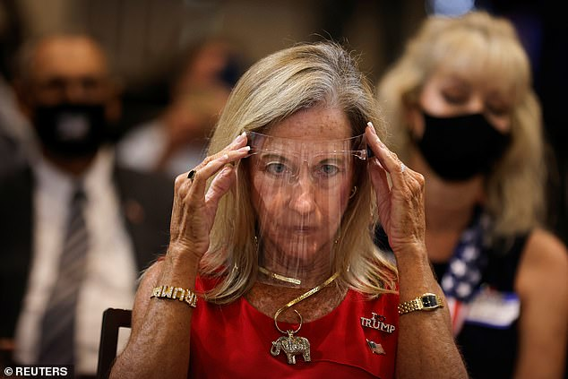 A supporter of President Donald Trump adjusts her facial shield during a campaign rally at Caloosa Sound Convention Center & Amphitheater in Fort Myers, Florida