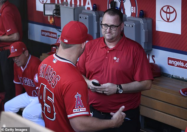 Mike Trout of the Los Angeles Angels speaks to Eric Kay in the dugout before playing against the Seattle Mariners at Angel Stadium of Anaheim on July 12, 2019 in Anaheim, California. Trout is wearing Skaggs's No. 45, as were all of his teammates, to honor the fallen pitcher