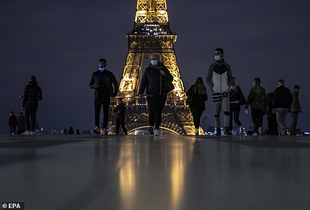 People wearing protective face masks walk near the Eiffel Tower hours before the new curfew