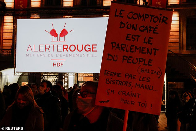 """A man holds a placard reading """"A bar is the parliament of people"""" at Charles de Gaulle square before the late-night curfew due to restrictions against the spread of the coronavirus disease"""